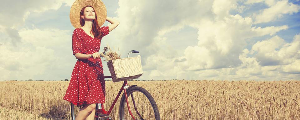 Roodharige meisje met fiets staat symbool voor de op tarweveld