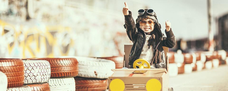 Een natuurlijk gezond kind blij aan het spelen in een trapauto zoals het na een CEASE & klassieke homeopathie behandeling waarbij de eventuele oxytocine-schade is weggenomen: een kind dat lekker in zijn vel zit